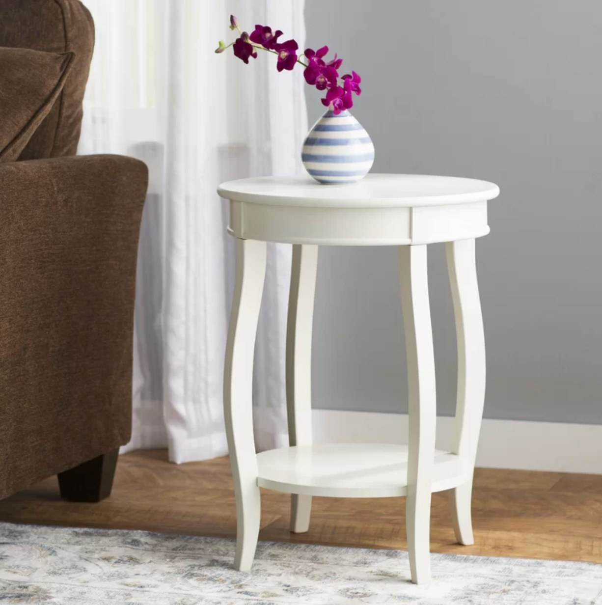 The side table in white being used as a vase holder