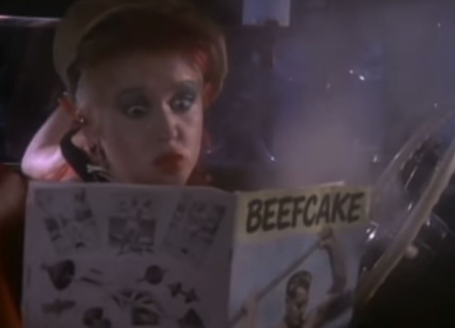 "Cyndi Lauper reading a ""Beefcake"" magazine in the front seat of her car for the ""She Bop"" music video"