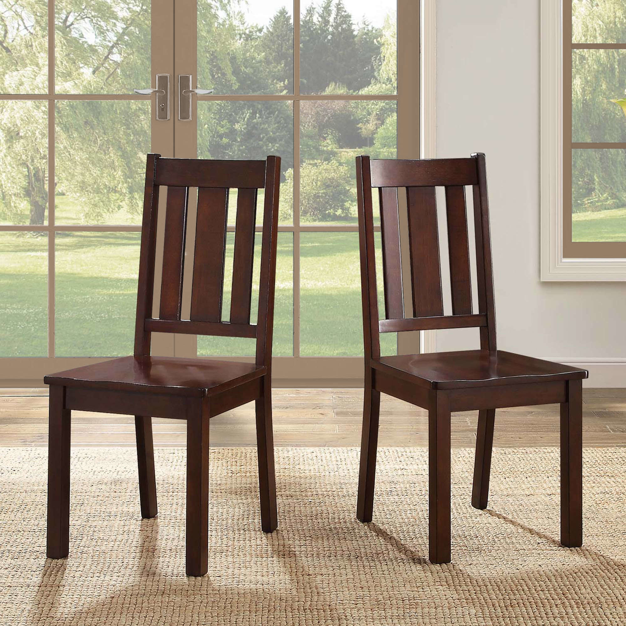 The dark brown dining chairs in front of a window
