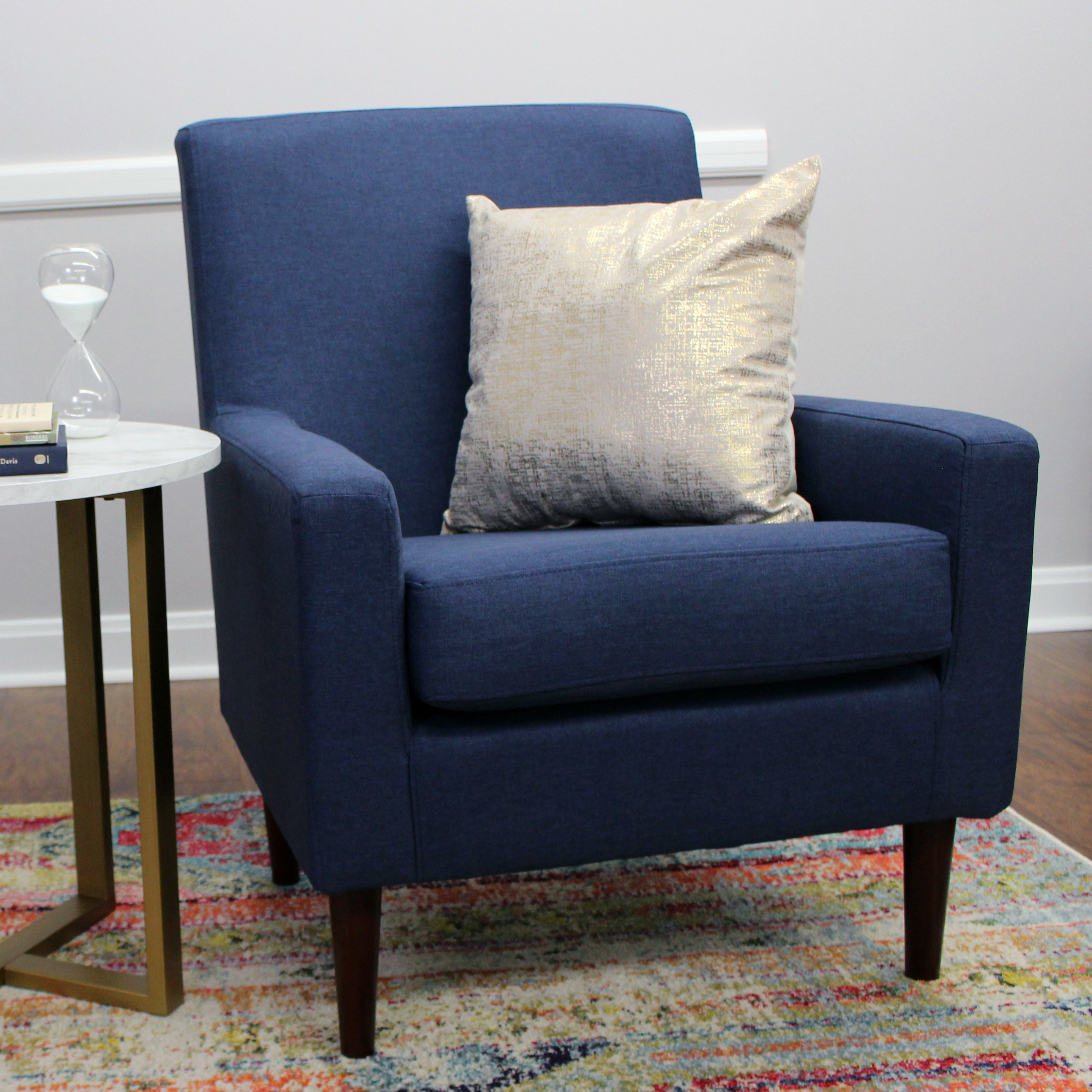 The blue chair, with a shimmery pillow