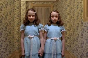 The twins from the movie The Shining standing at the end of the hallway