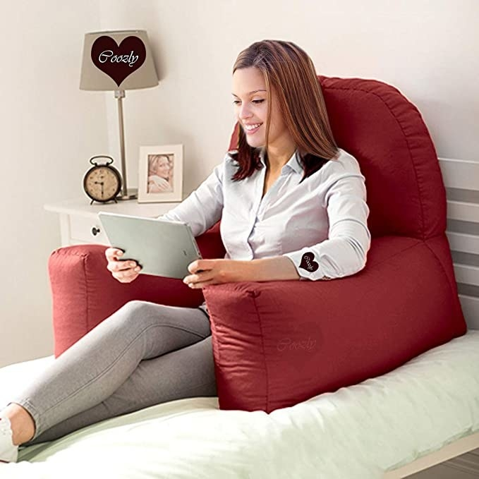 A woman sitting on the chair cushion on her bed with a tablet in her hands.
