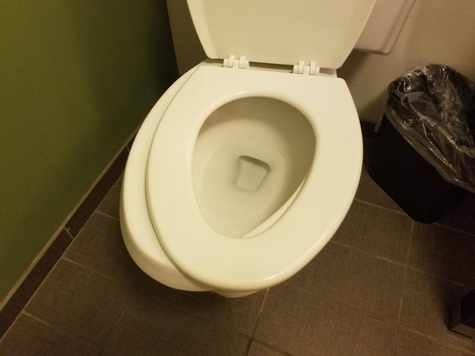 A toilet seat that's crooked because it isn't screwed on tightly enough