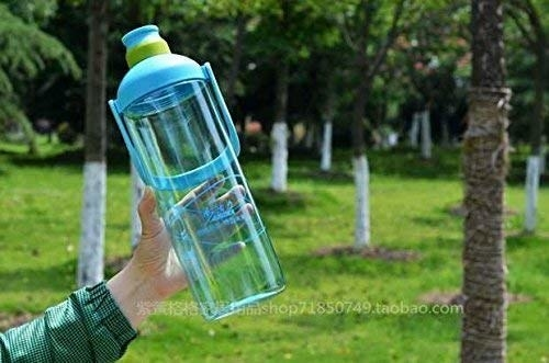 A person's hand holding the water bottle in a park.