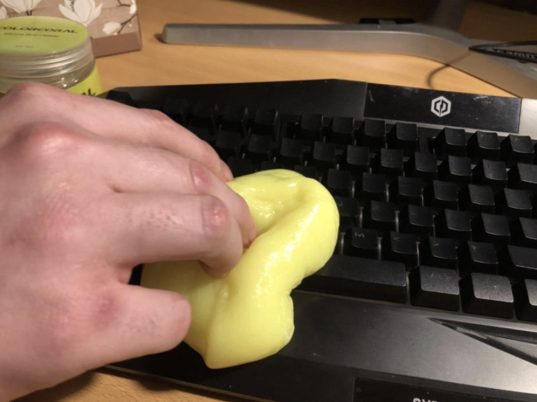 a reviewer using the yellow putty to cleaner their keyboard