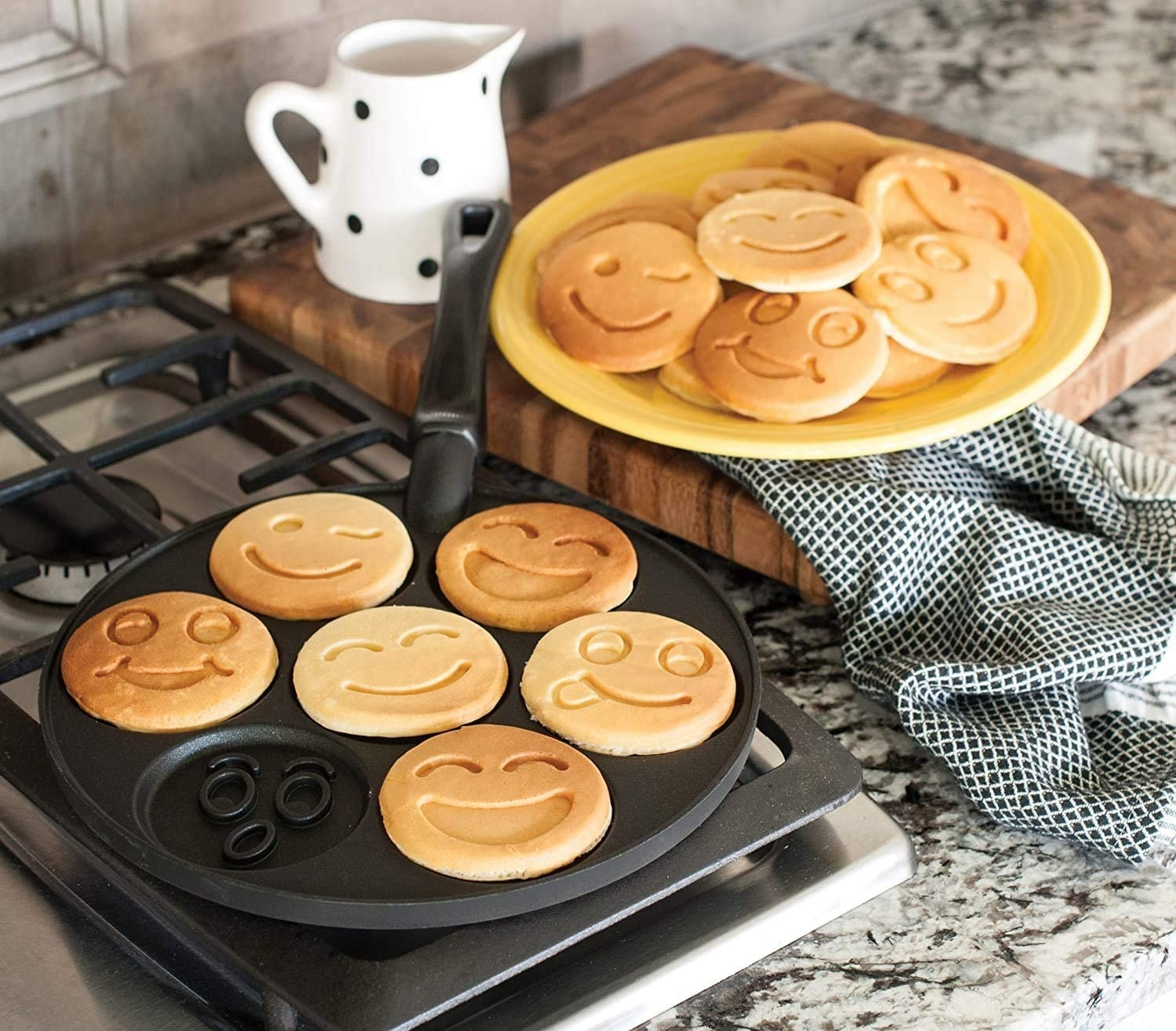 Smiley face pancakes on the griddle and on a plate