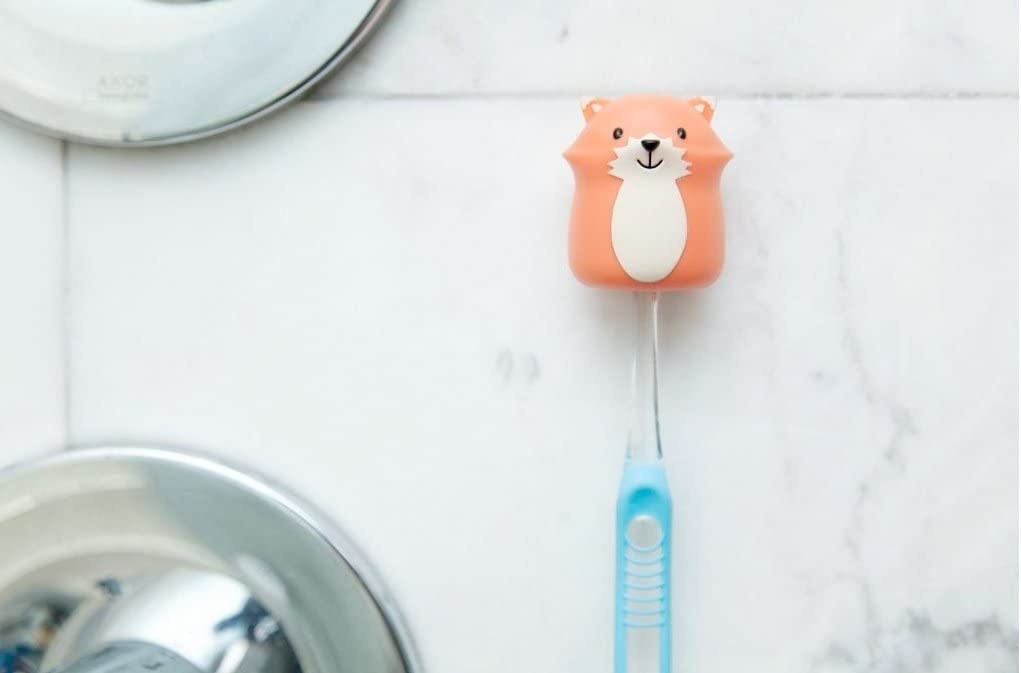 The toothbrush holder holding a toothbrush against a wall