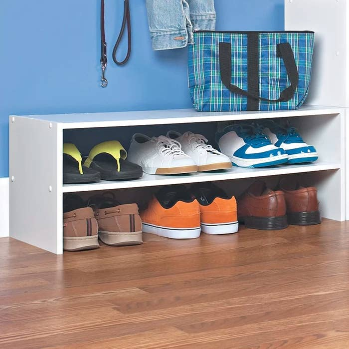 The white shoe rack holding sneakers, sandals, and loafers
