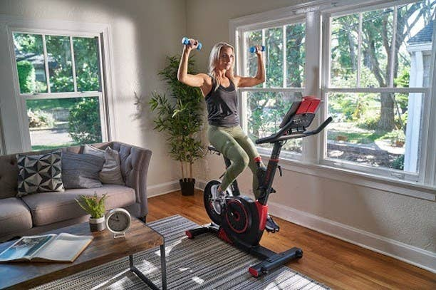 Woman riding Echelon bike in her living room with weights in her hands