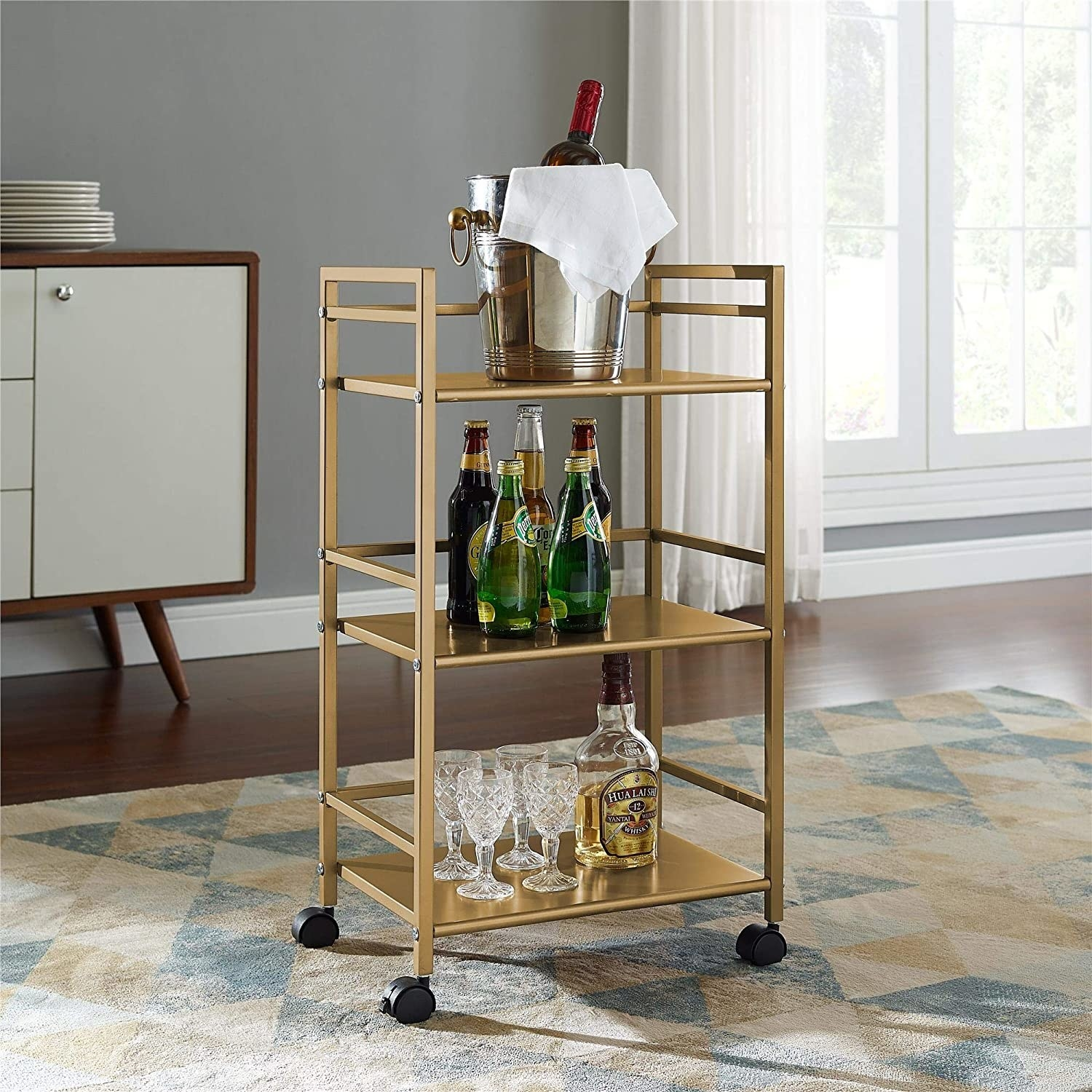 golden utility cart with four black wheels and three open shelves. The cart has wine bottles and glasses on it.