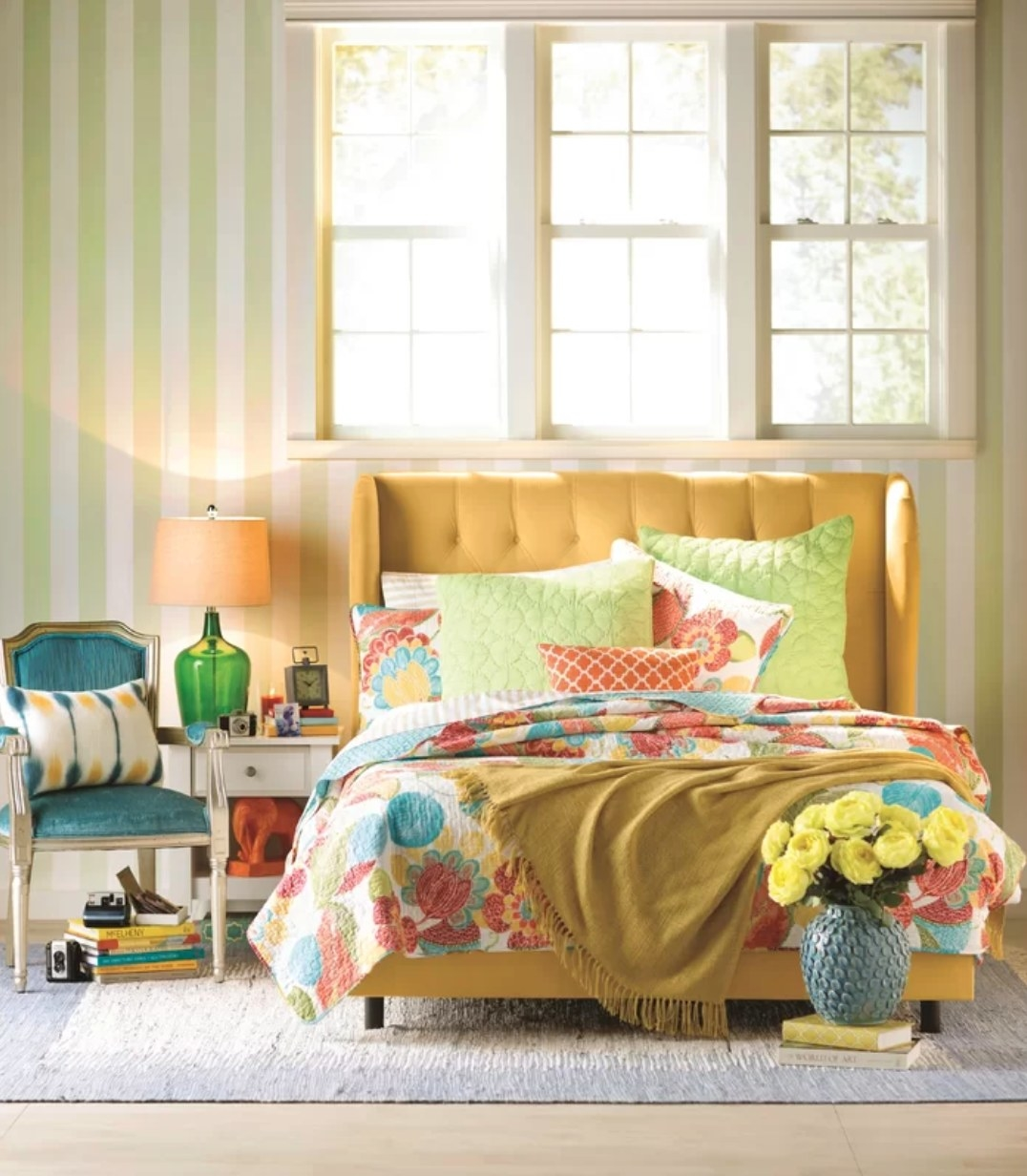 The blanket in yellow draped across a bed