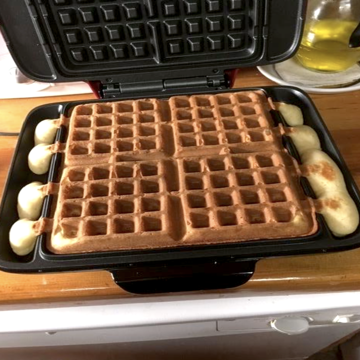 Reviewer image of the waffle maker open, showing how the overflow channel on the sides catch batter