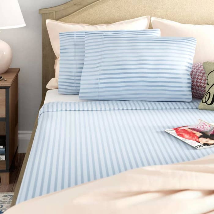 The sheets in blue stripe on a bed