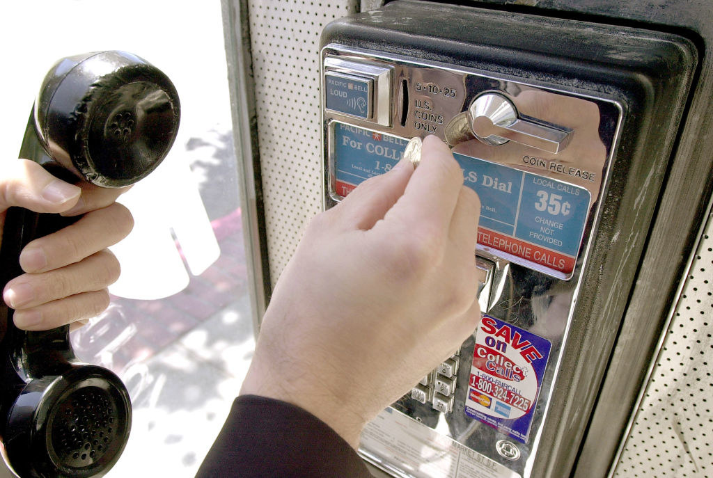 A hand holding the receiver and putting a quarter into the payphone