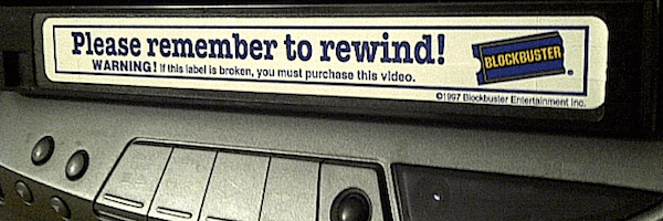 "Blockbuster VHS tape with the sticker ""Please remember to rewind"" sticking out of the VCR"
