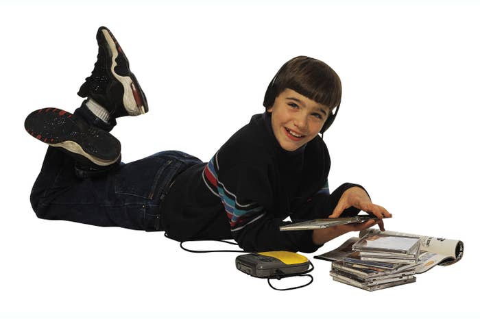 A '90s kids laying on the floor listening to a CD from his yellow portable CD player while he has a CD case opened in his hand and has a stack of CDs next to him