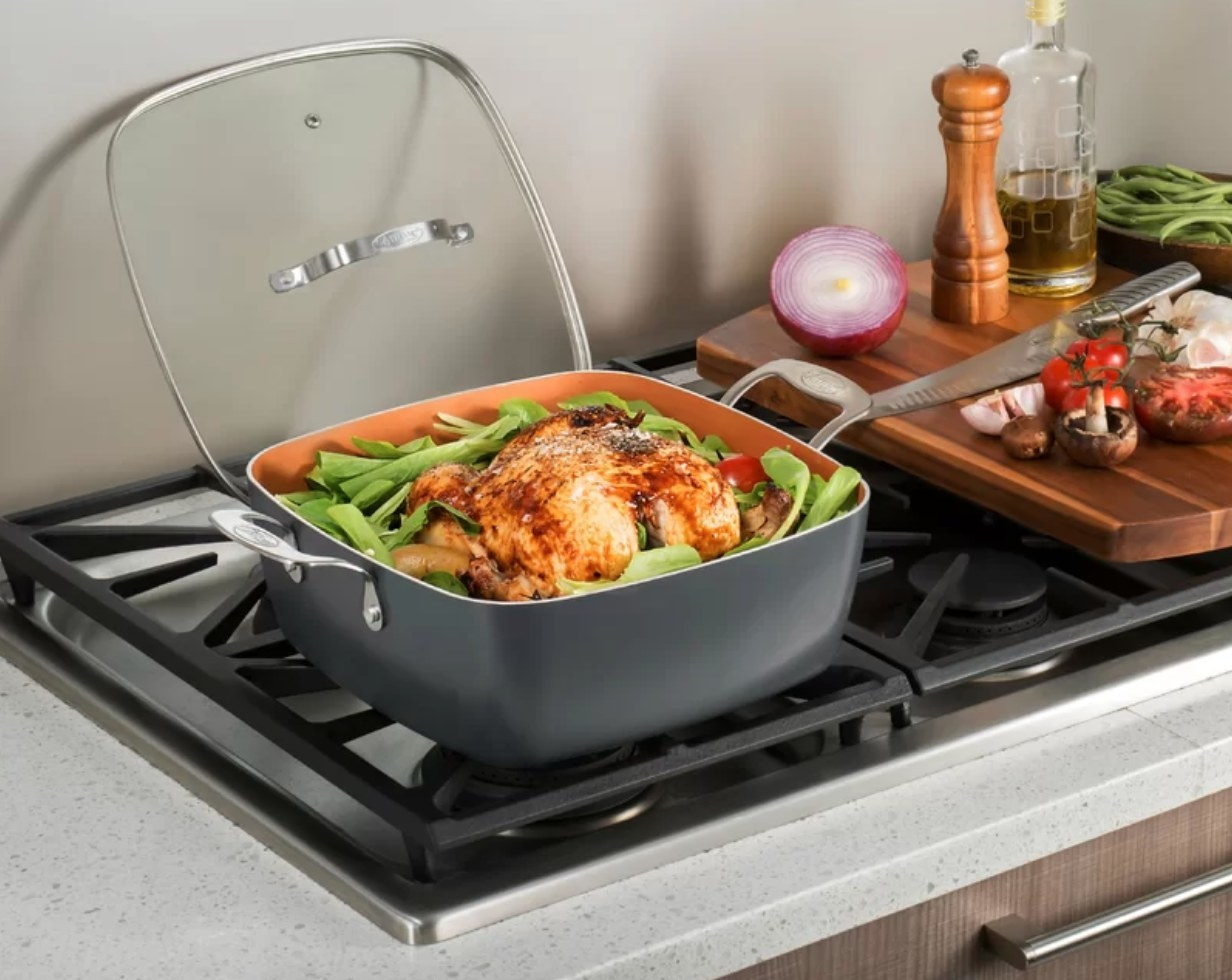 The pan being used to cook chicken and greens