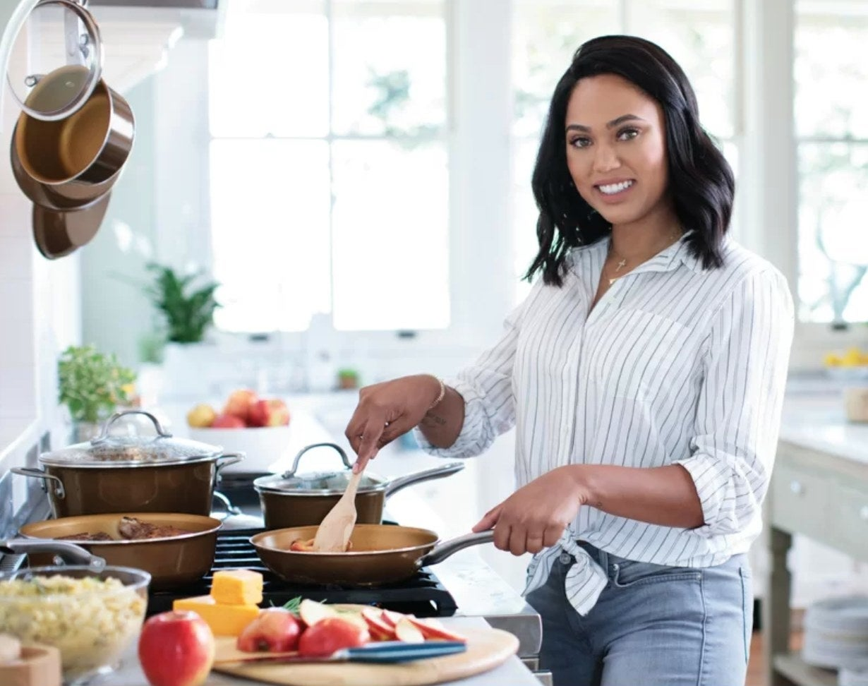 Ayesha Curry using several of the pots and pans from the set