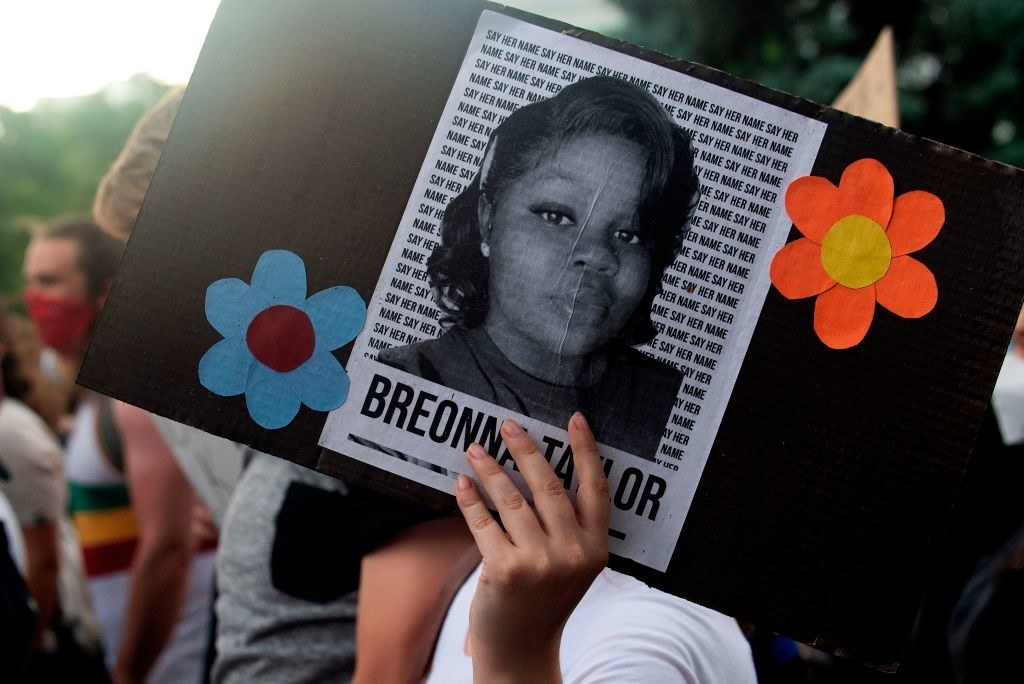 A protestor holding a sign with Breonna Taylor's picture