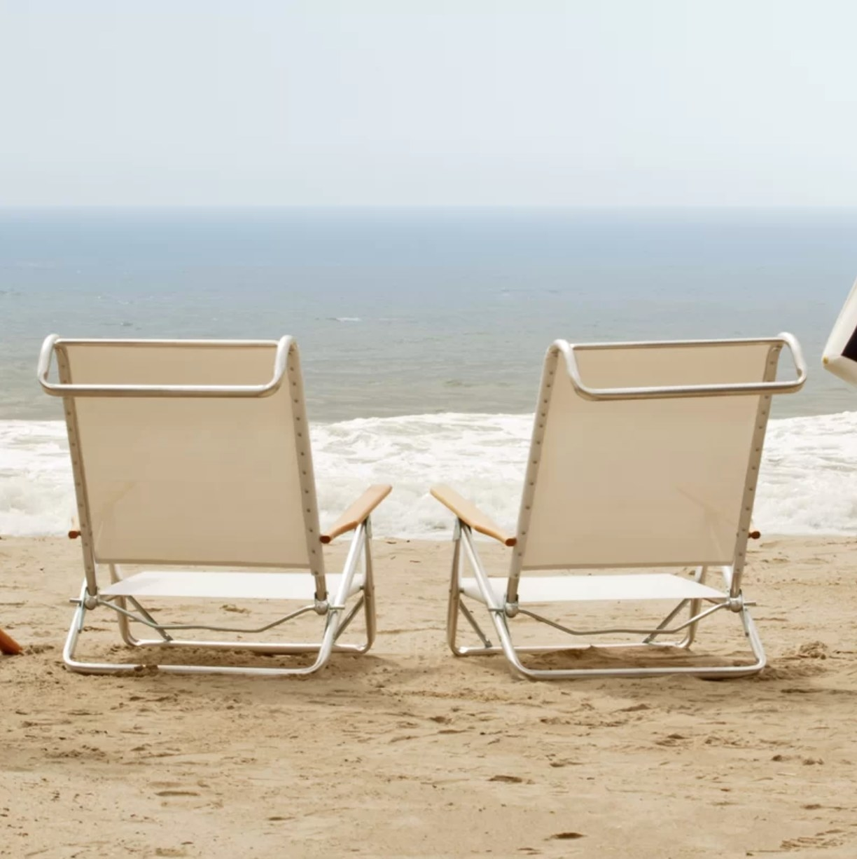 Two cream-colored beach chairs