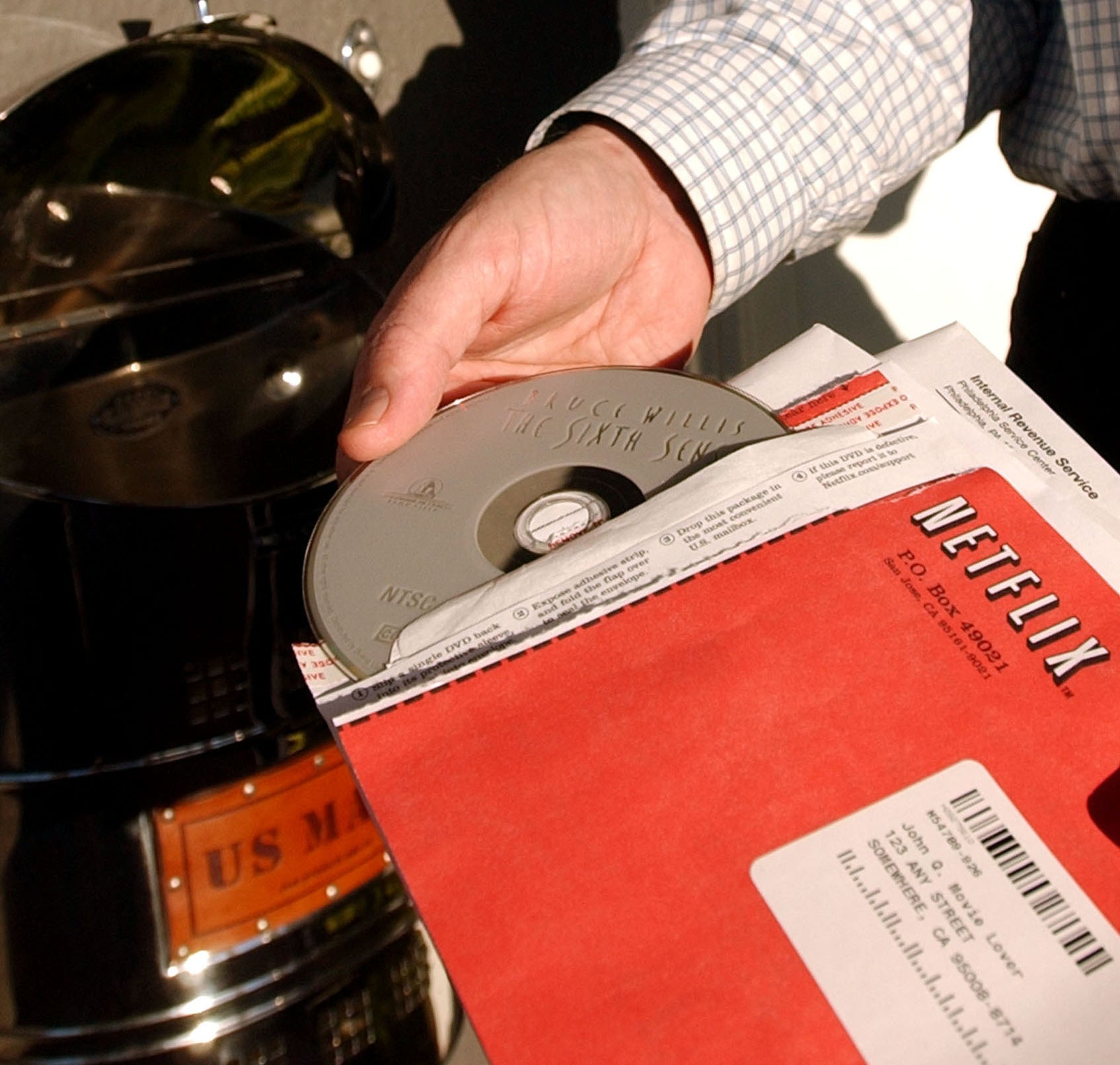 "A photo of a man pulling a ""The Sixth Sense"" out a red Netflix envelope"