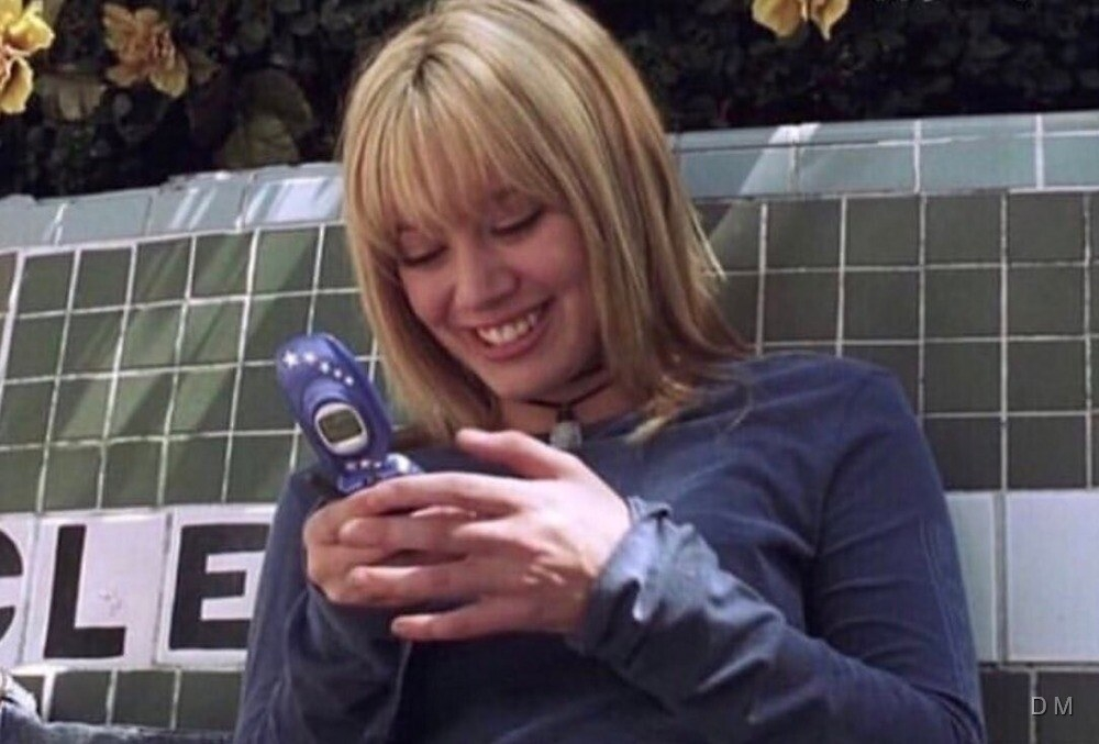 A screenshot of Lizzie McGuire texting on a blue flip phone
