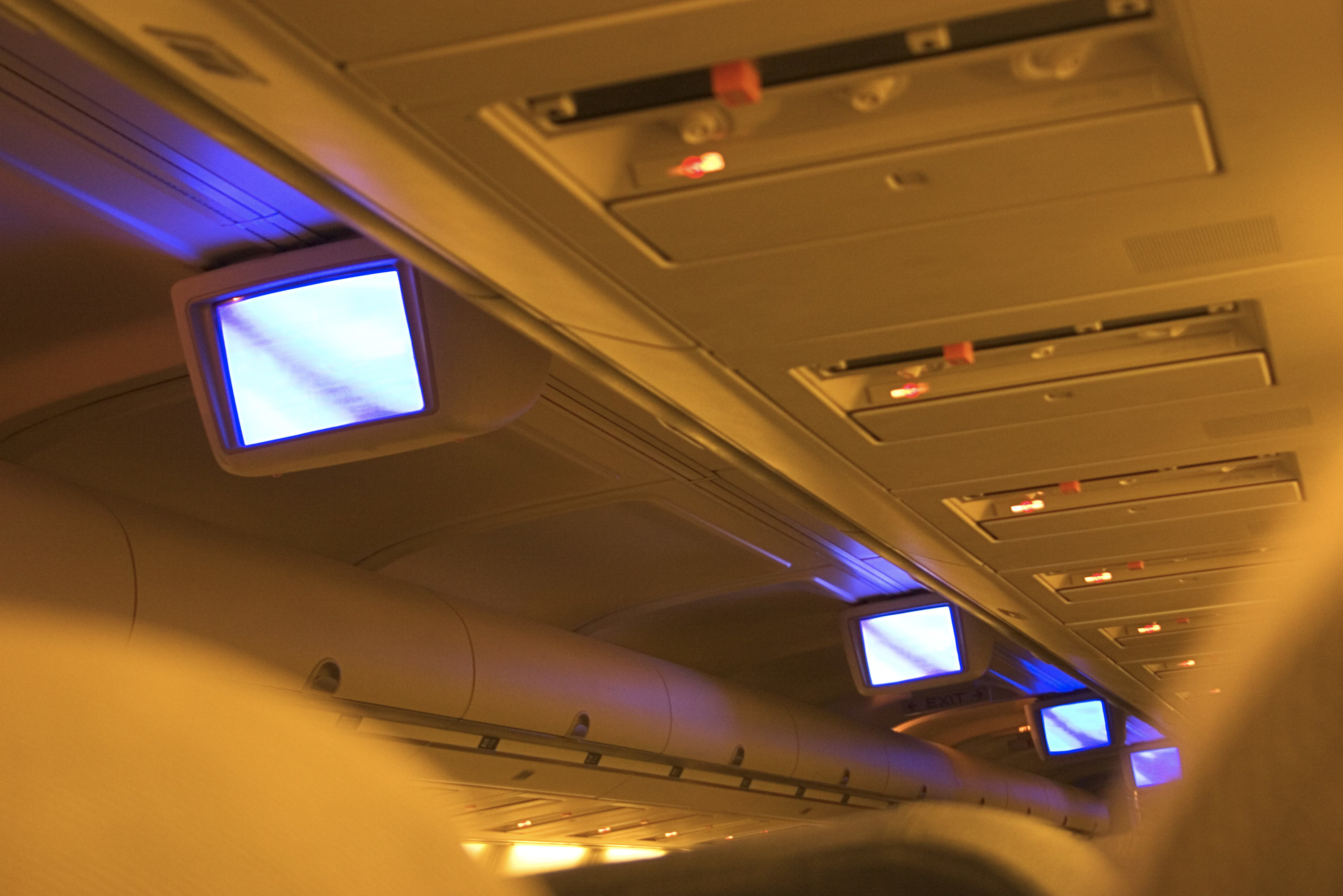 A '90s plane with TV monitors hanging from the aisle