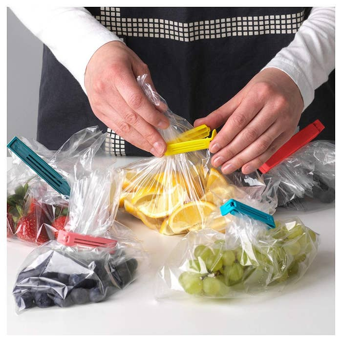 A person's hand using the baggie seals to clip a clear plastic bag of lemons, surrounded by already sealed bags of several fruits.