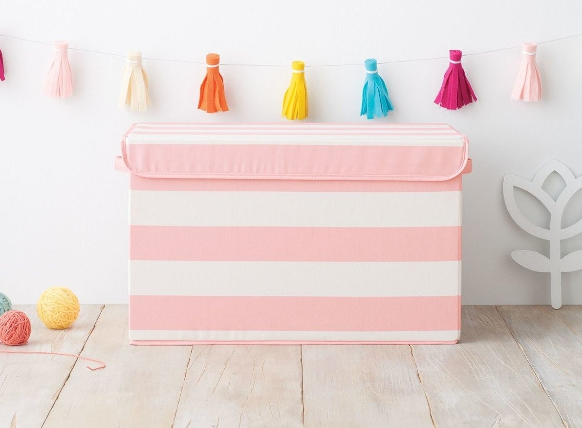 Pink and white striped toy bin in a nursery