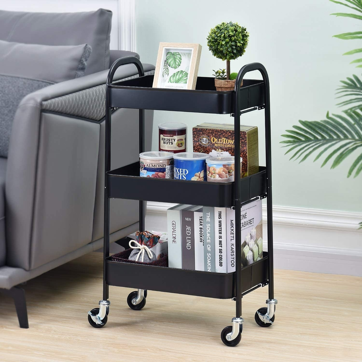 A utility cart with books, snacks, and decor accessories on it