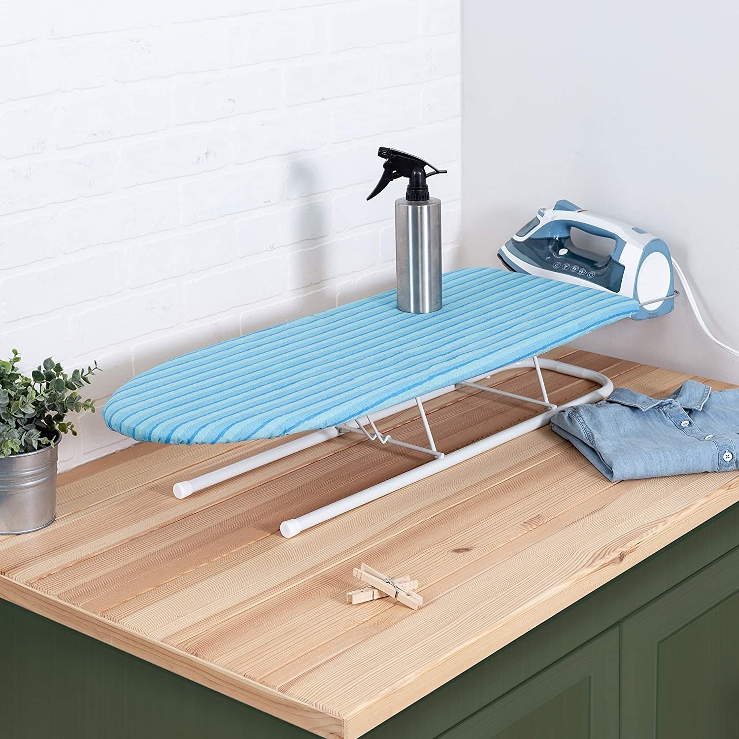 The ironing board on a countertop with a spray bottle on top of it