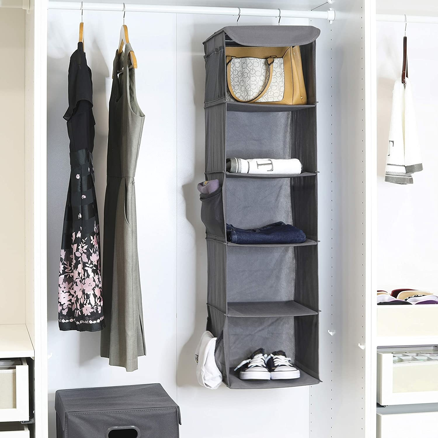 The closet organizer hanging in a closet with shoes, towels, and handbags on its shelves