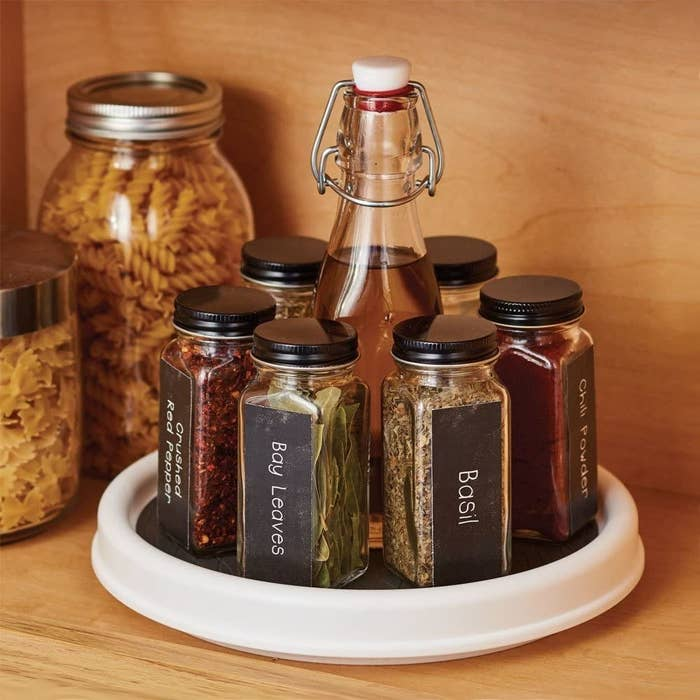 inside a kitchen cabinet with a clear lazy susan turntable containing jars of various spices within reach