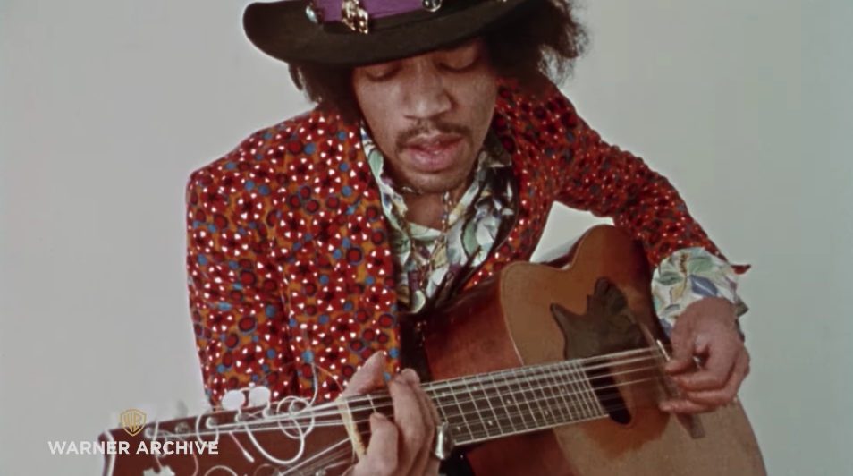Jimi Hendrix playing acoustic guitar while wearing a hat and colorful clothing