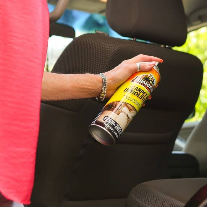 A person spraying carpet cleaner onto the car seats