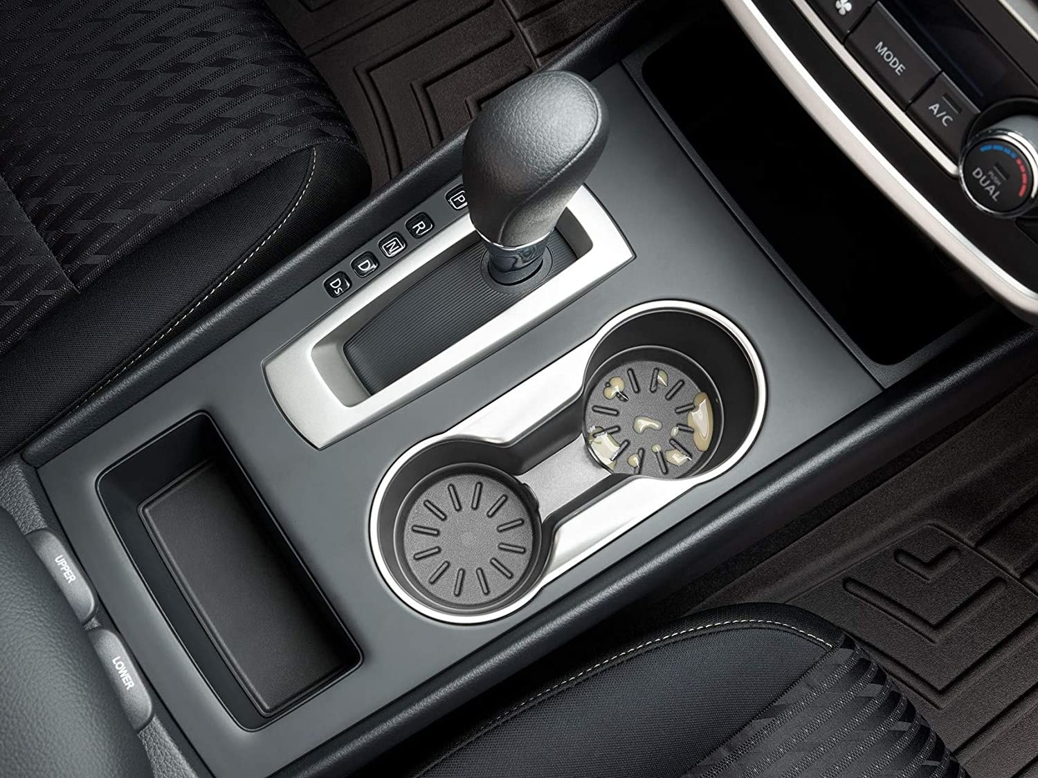 A car console with removable coasters in the cup holders