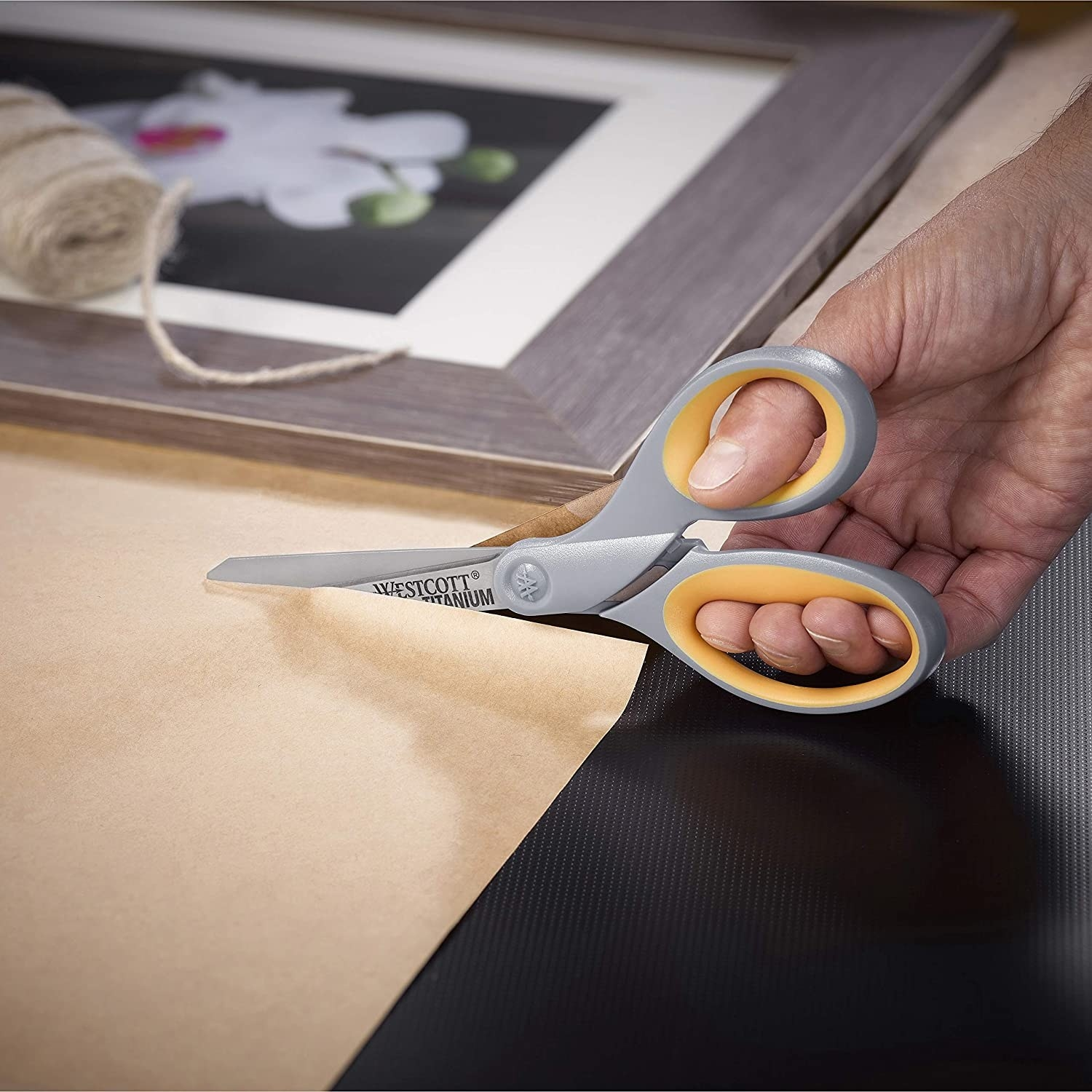 A model's hand using a pair of gray and orange scissors