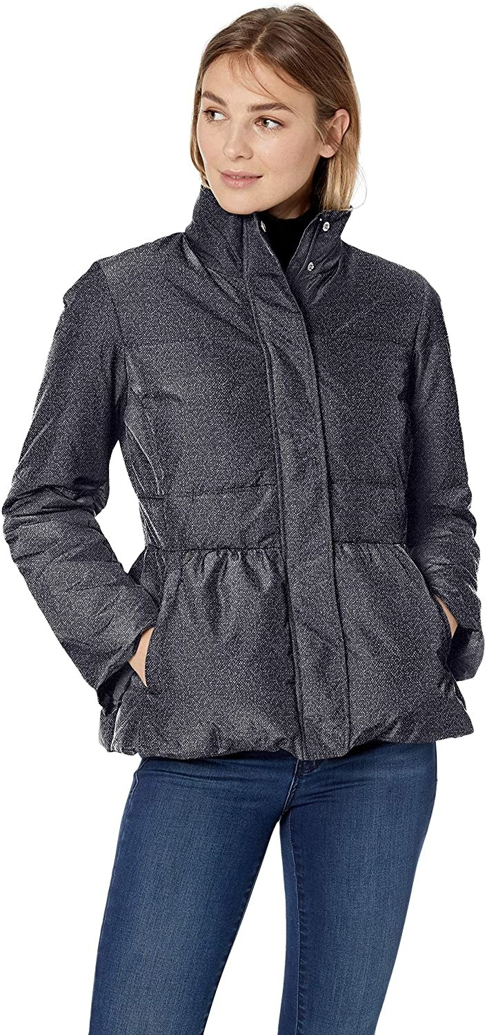 Model wearing the puffer-style jacket with a peplum on the bottom half and pockets and a zipper with buttons down the front in a black color with tiny white specks all over it