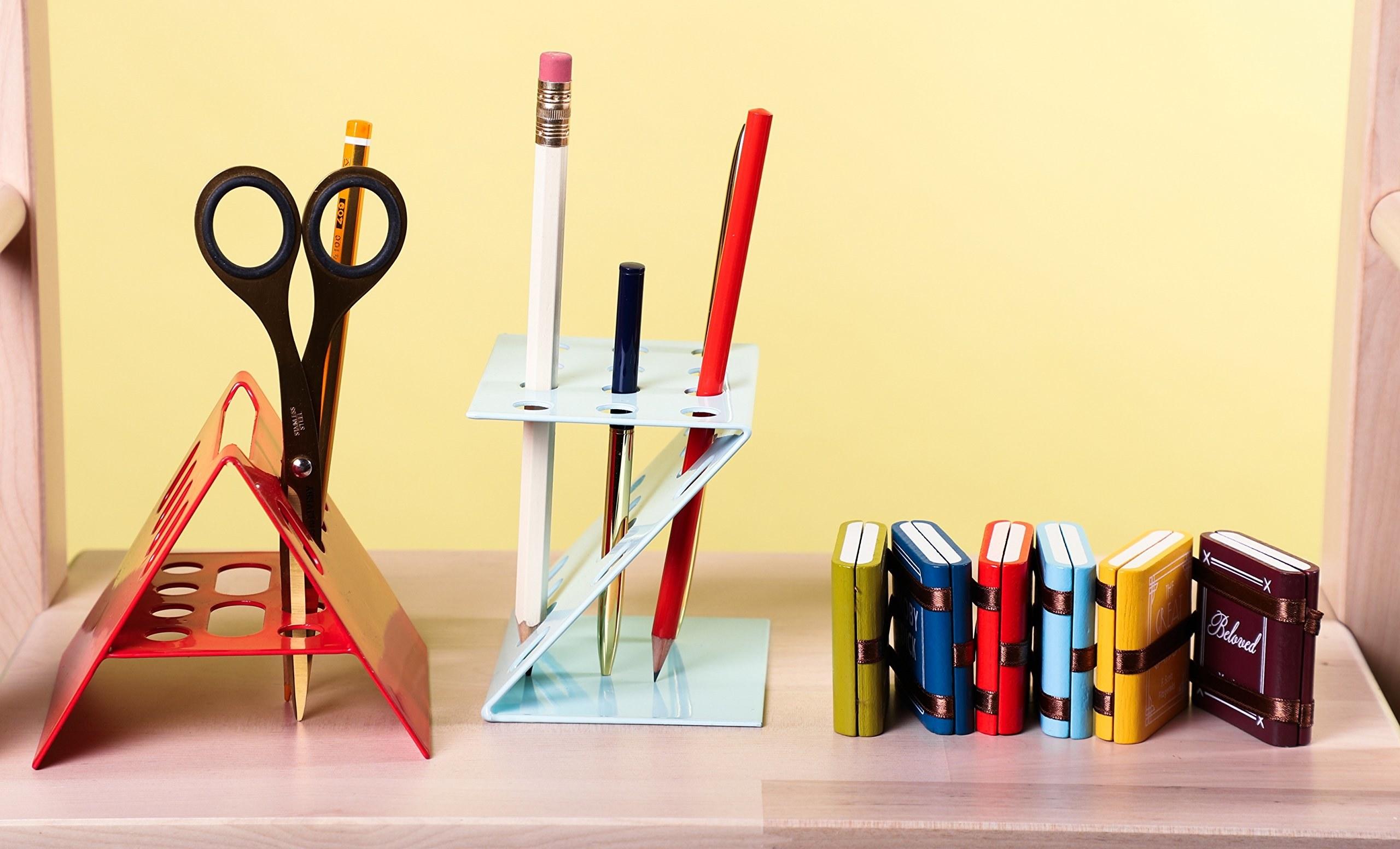 A set of miniature books kept beside pen stands.