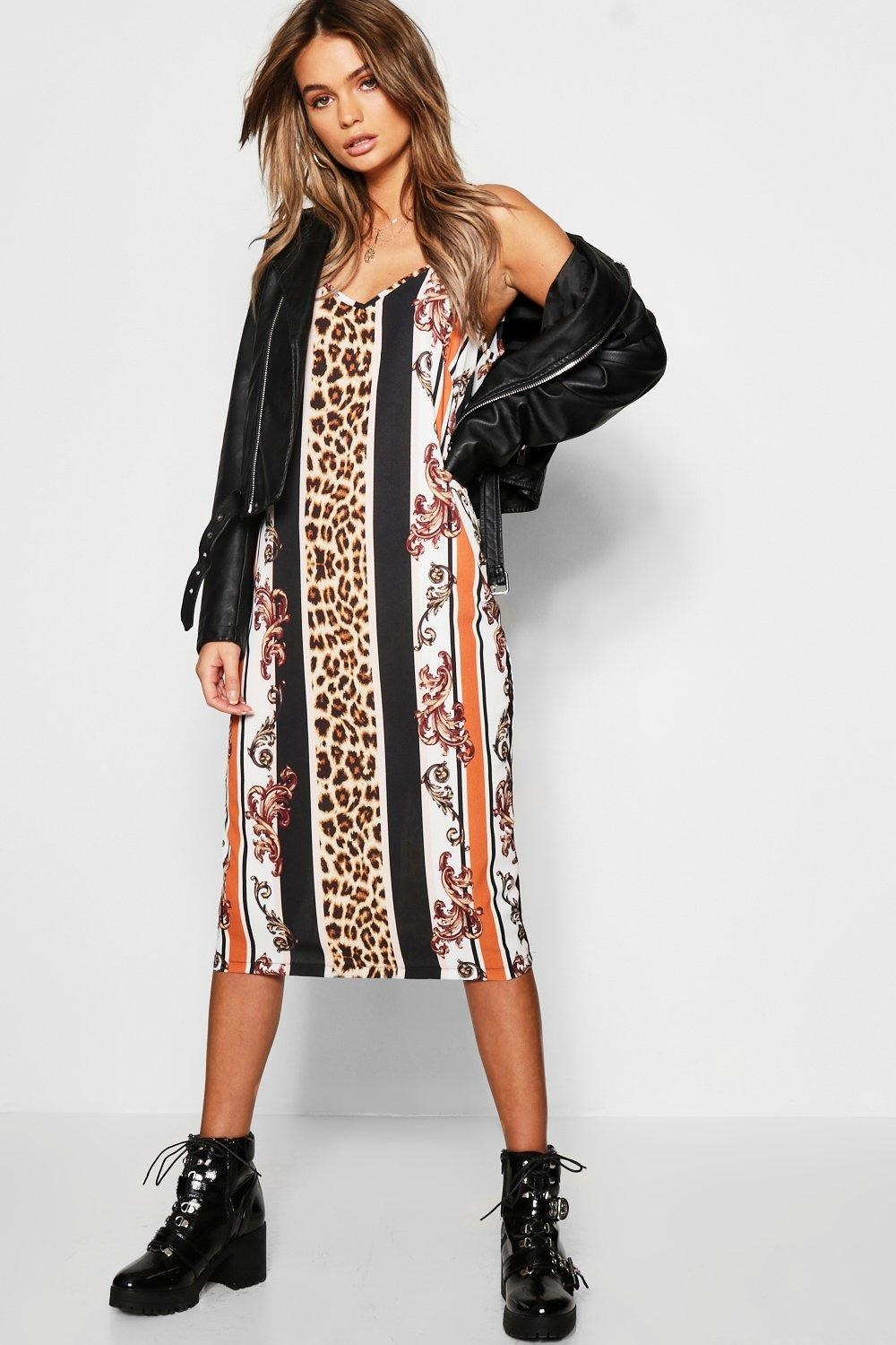 Multi-pattern dress with stripes of animal print, filigree, black, and orange. Worn with black ankle-high boots and leather jacket.
