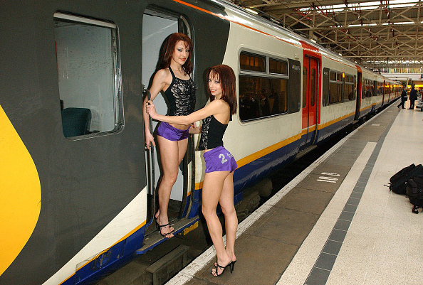 two girls posing outside of train