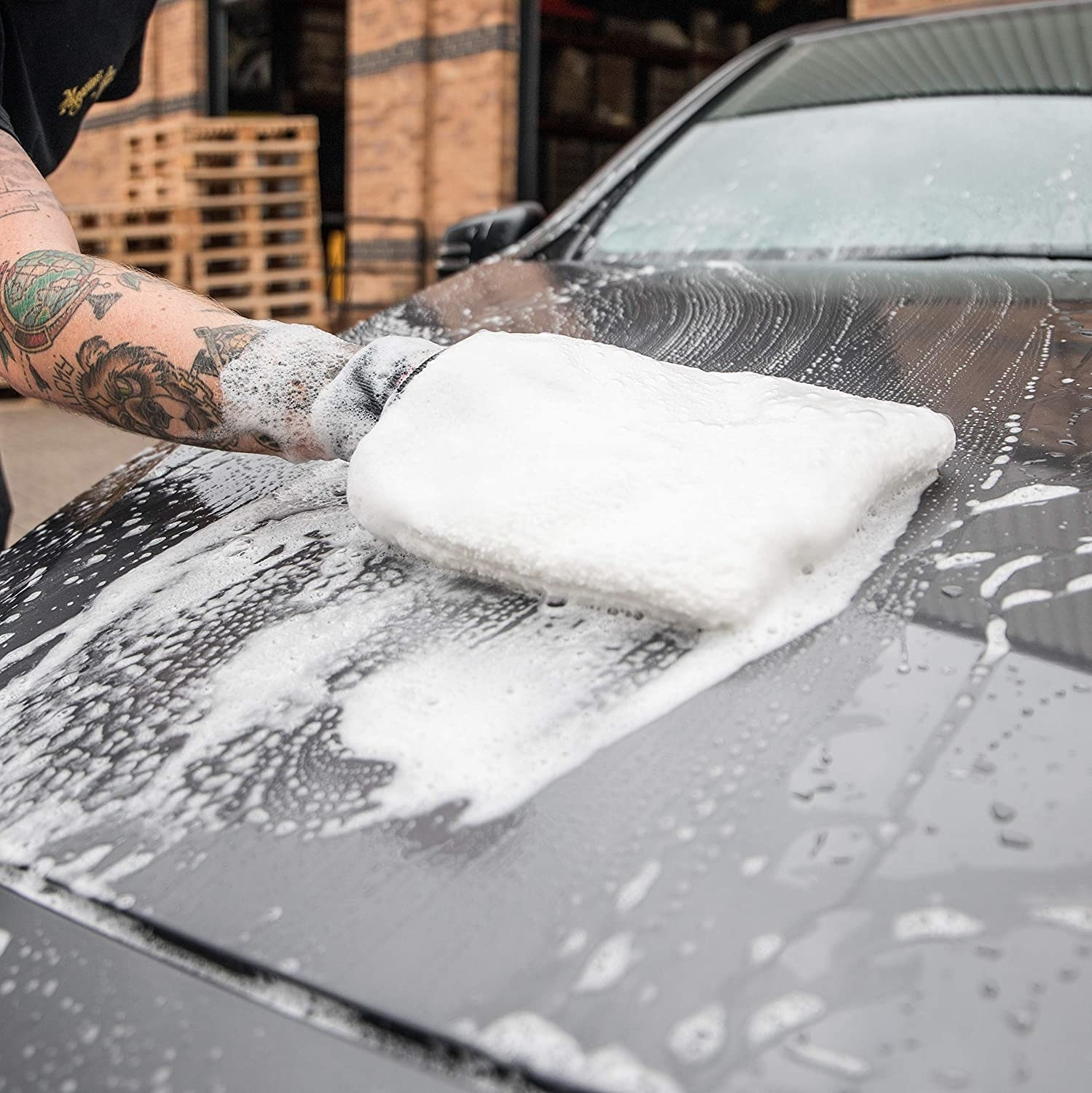 A person wearing a large fluffy wet mitt to wash their car
