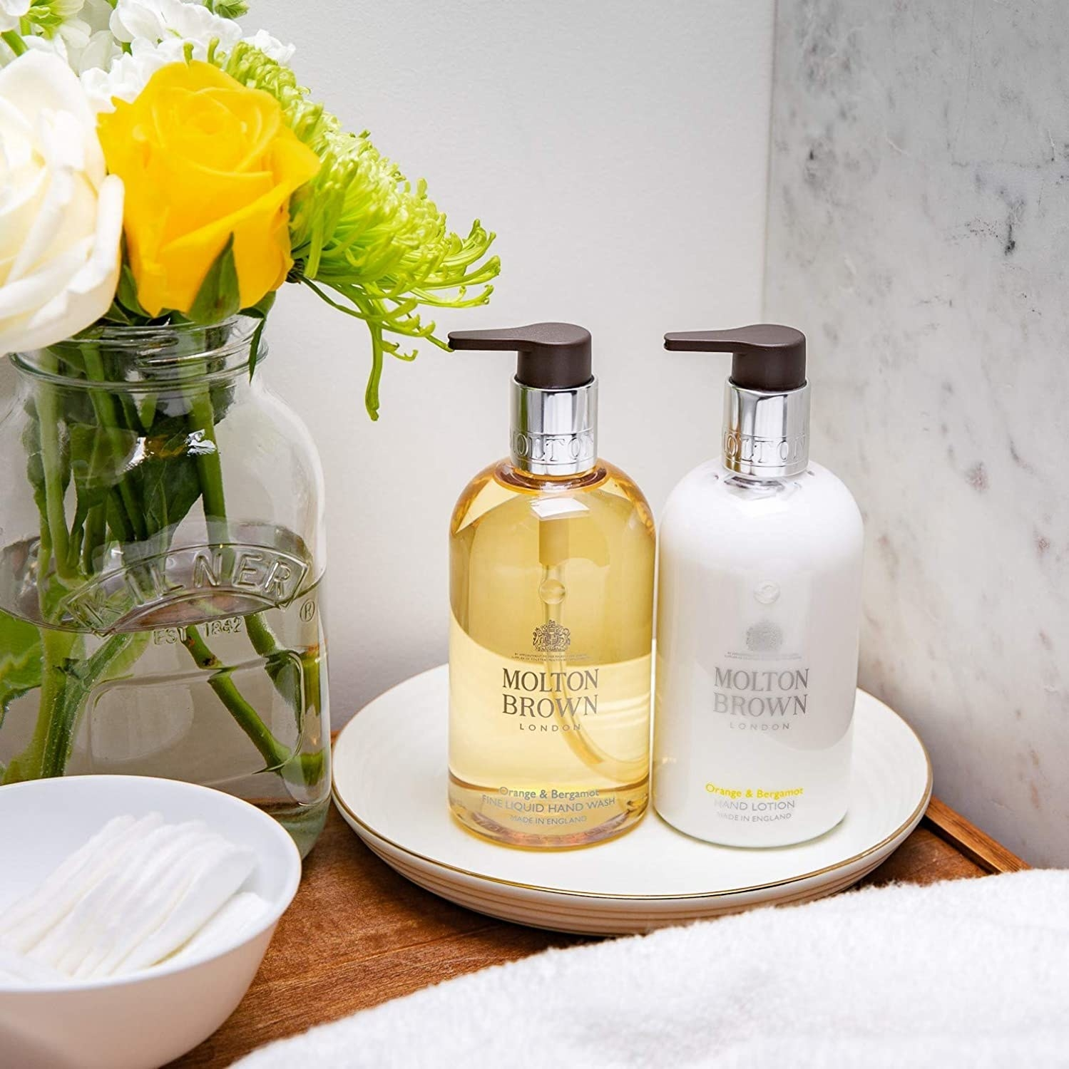 A duo of Molton brown hand soap and hand lotion on a tray in a bathroom.