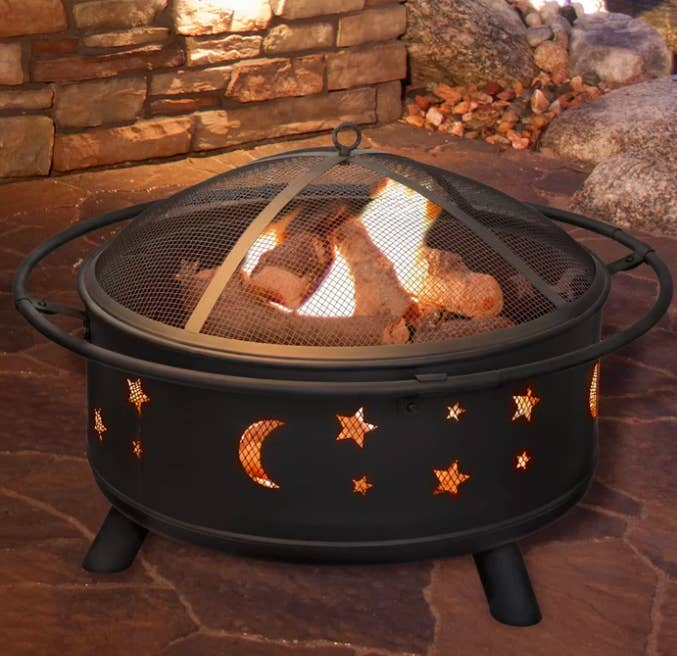 Star and moon-printed black fire pit with burning wood on an outdoor patio