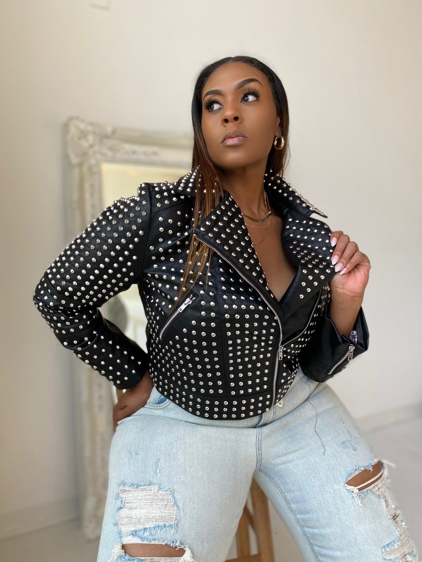 Model wearing the cropped faux leather jacket with silver studs over the whole thing with diagonal pockets on the side and a zip-front.