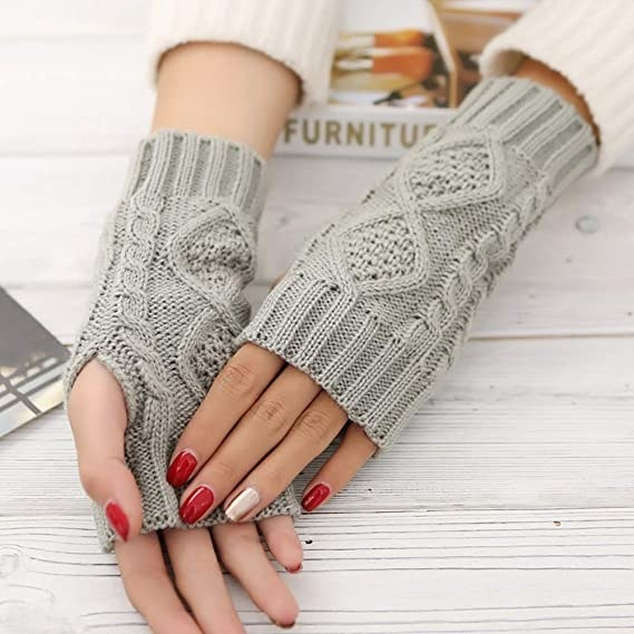 person's hands with light gray sweater-like wrist warmers that are about six inches long but leave room for lots of hand and finger movement