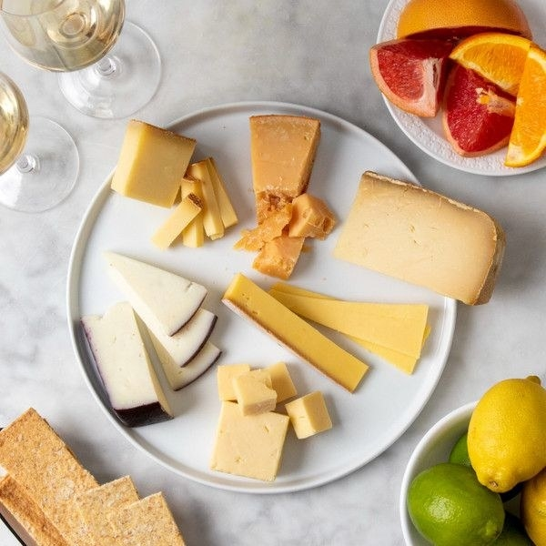 A plate with several different kinds of cheese surrounded by crackers, fruit, and wine.