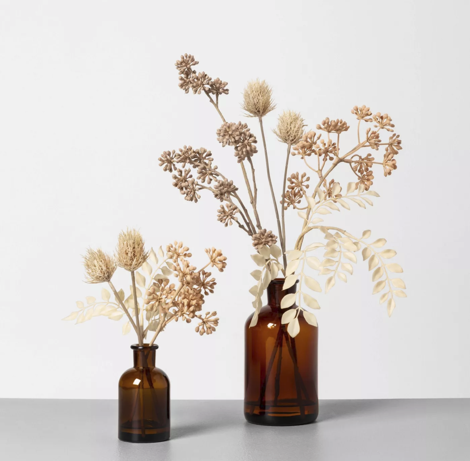 two vases (one bigger) with white thistle and sedum flowers in them