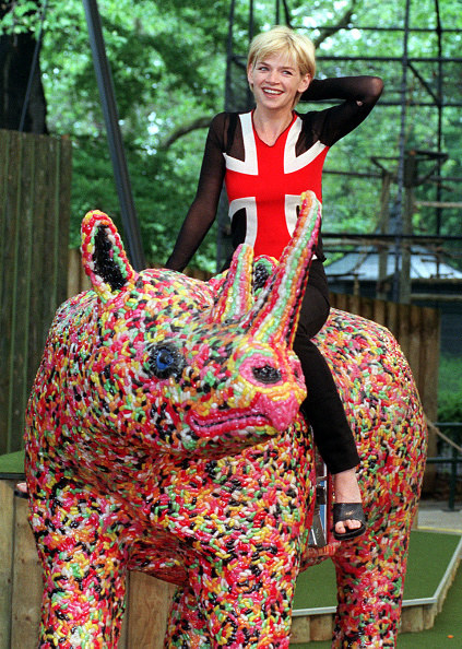 woman sat on rhino statue made of jelly beans