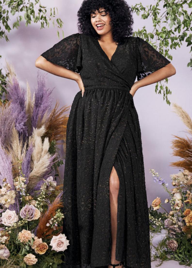 Model in V-neck black wrap dress with sheer sleeves and beaded embellishing
